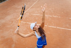 Tennis ball serving. Correct stance and practiced movements are essential for a good shot. A talented tennis player woman has been performing a well-trained movement for years. Ball up to the sky.