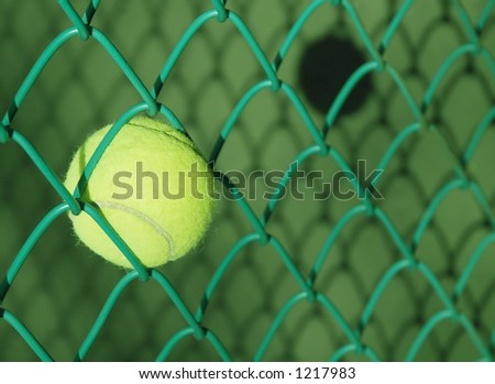 Tennis ball stuck in chain-link fence and shadows on tennis court