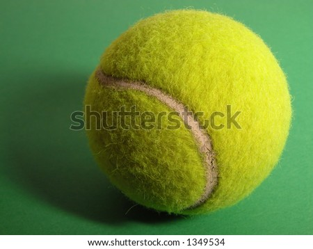 Tennis ball with shadow on a green surface.