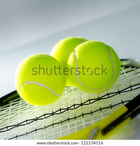 Tennis balls and racket against a white background