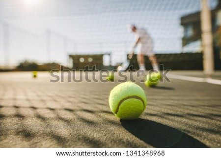Tennis balls lying on the ground on a tennis court. Man playing tennis on a sunny day with tennis balls lying on the court.