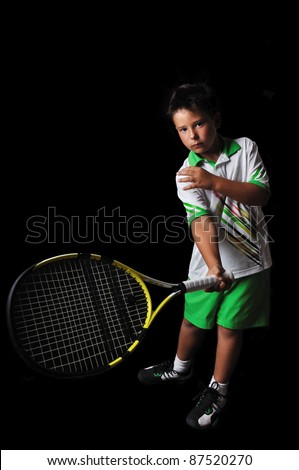 Tennis boy playing forehand isolated in black