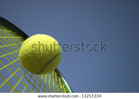 Tennis - Close up of a tennis ball and racket sky blue