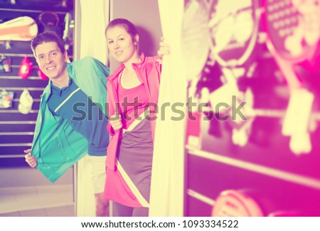 Tennis couple is standing in modern tennis wear in the fitting room in the store.