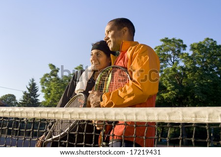 Tennis couple standing at the net holding their rackets and smiling. Horizontally framed photo.