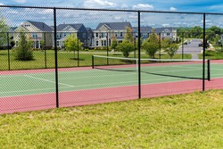 tennis court in a residential area. green lawn and houses under the blue sky.