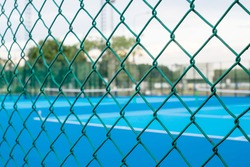 Tennis court  in blurry for background , Steel wire mesh fence on blurred background
