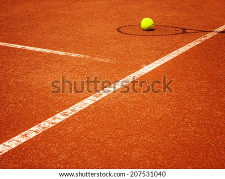tennis court t-line with racket shadow and ball