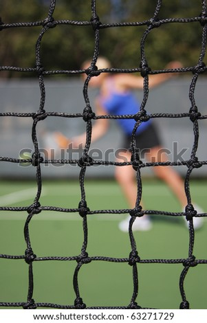Tennis net with player returning serve in the background