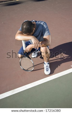 Tennis player crouching down looking defeated and sad, he holds his tennis racket and hangs his head in shame. Vertically framed photo.
