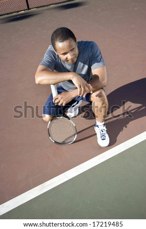 Tennis player crouching down looking defeated and sad, he holds his tennis racket and rests his arms on his knees. Vertically framed photo.