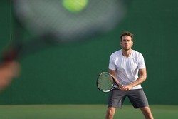 Tennis player focused on other player hitting ball with racket on court. Men sport athletes players playing tennis match together. Two professional tennis players on hard outdoor court during game.