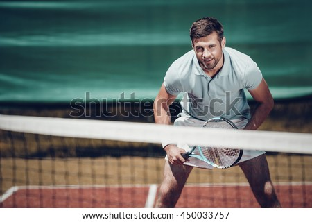 Tennis player. Handsome young man in polo shirt holding tennis racket and smiling while standing on tennis court