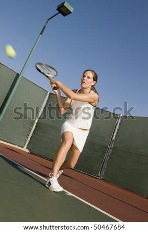 Tennis Player Hitting Backhand on tennis court