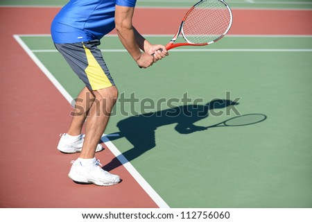 Tennis Player holding racket casting shadow on court