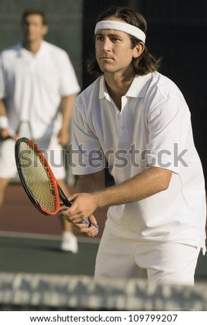 Tennis player holding racket with partner standing in the background