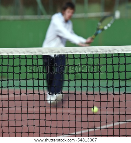 Tennis player in action (selective focus, focus on the net)