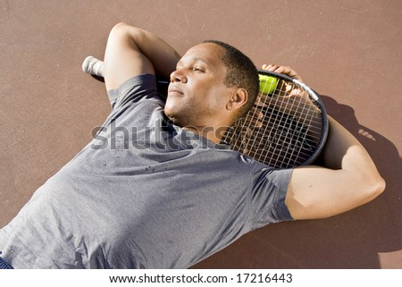 Tennis player laying down on the court with his ball and racket relaxing. Horizontally framed photo.