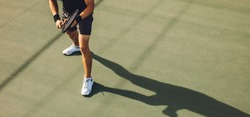 Tennis player playing tennis on hard court. Young man in sports wear standing on hard tennis court ready to return the serve during a game.