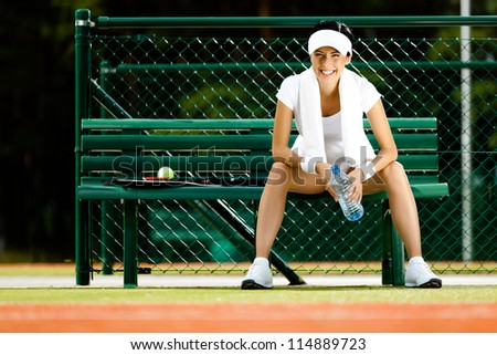 Tennis player rests with bottle of water on the bench at the tennis court