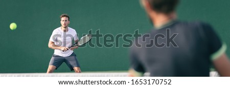 Tennis players playing on green court man focused on other player hitting ball with racket panoramic. Men sport athletes playing tennis match. Two professional tennis players outdoor during game.