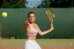 Tennis playing sportive woman hitting ball on red hard court. Caucasian athlete girl returning serve with racket wearing white skirt and pink shoes.