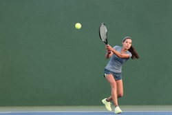 Tennis playing woman hitting ball on green hard court. Asian athlete girl returning serve with racket wearing skort and shoes.