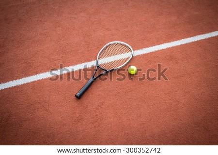 Tennis racket near a yellow ball on a brick red court