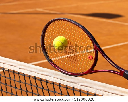 tennis racket on the net in the middle of the tennis court