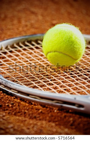Tennis racket with ball  on it clay on clay court