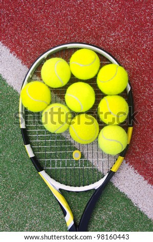 tennis racket with balls on court