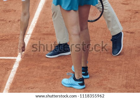 Tennis umpire points with finger out next to the line, with player watching, standing next to him