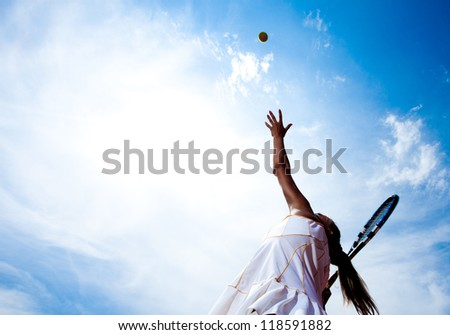Tennis woman in a white tennis dress developing ball service
