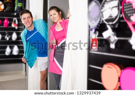 Tennis young couple is standing in modern tennis wear in the fitting room in the store.