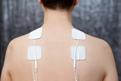 TENS therapy in fibromyalgia treatment - electrodes placed on female patient's shoulders.