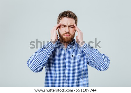 Tensed bearded young man touching his temples and having headache #551189944