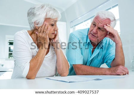 Tensed senior man and woman talking to each other at home