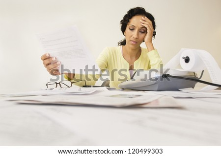Tensed woman with expense receipt sitting at home