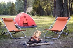 Tent and campfire in nature with two deckchairs. Camping in nature lifestyle concept.