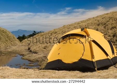 Tent and small lake in high mountain.