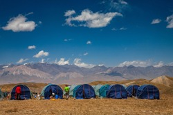 Tent camp in the mountains. Scenic landscape of Kyrgyz nature. Pamir Mountain System. Lenin Peak base camp.