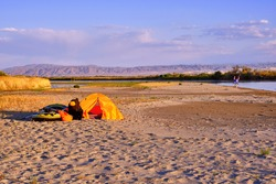 Tent camp with equipment and inflatable boat on the sandy shore of the river at sunrise in summer season