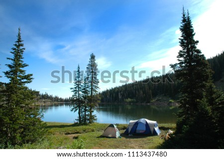Tent camping by lake in wilderness for recreation purposes
