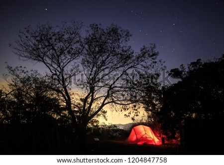 Tent glows red against distant glow from city and starry night sky #1204847758