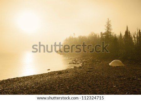 Tent in early morning sun and fog on Lake Superior in Minnesota