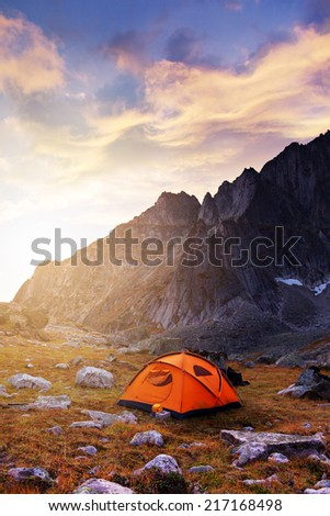 Tent in mountains at beautiful sunrise