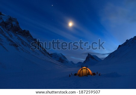 Tent in the mountains on a winter night with bright moon in Lapland.