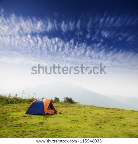 tent on a grass under white clouds