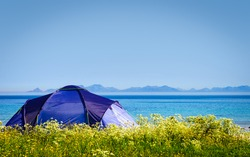 Tent on beach seashore in summer. Camping on ocean shore. Lofoten archipelago Norway. Holidays and travel.