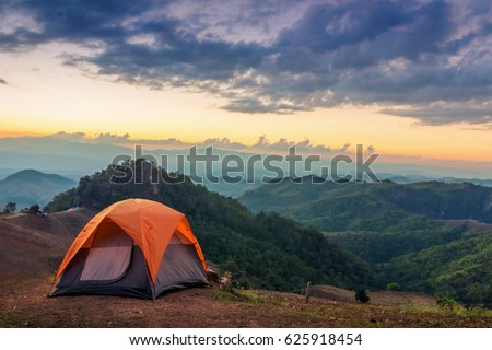 Tent on the hill beneath the mountains under dramatic sky #625918454